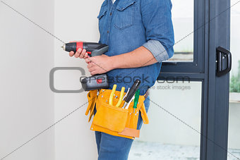 Mid section of a handyman with drill and toolbelt