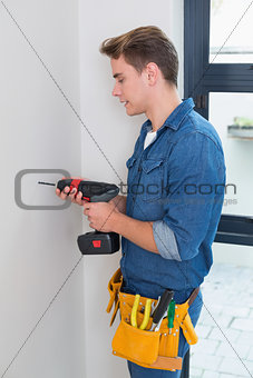 Handyman using a drill with toolbelt around waist