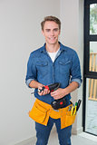 Handyman holding a drill with toolbelt around waist