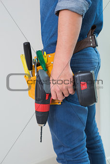 Side view mid section of a handyman with drill and toolbelt