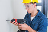 Serious young handyman using a drill