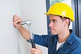 Handyman hammering nail in wall