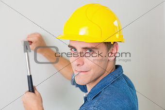 Close up of a handyman hammering nail in wall