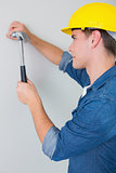 Side view of handyman hammering nail in wall