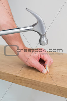 Hands hammering nail in wooden bench