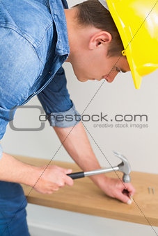 Handyman hammering nail in wooden bench
