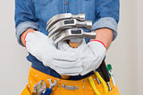 Mid section of handyman holding hammers with toolbelt around waist