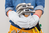 Mid section of a handyman holding hammers with toolbelt around waist