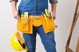 Mid section of handyman with toolbelt and hard hat
