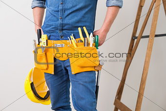 Mid section of a handyman with toolbelt and hard hat