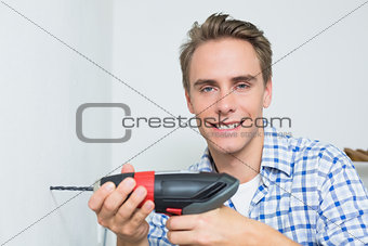 Portrait of handyman using a cordless drill to the wall