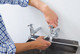 Close up of a plumber's hand and washbasin