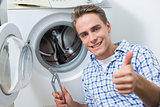 Technician repairing washing machine while gesturing thumbs up