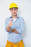 Handyman in yellow hard hat gesturing thumbs up