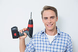Smiling handsome young handyman holding drill