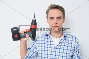 Portrait of a serious handsome young handyman holding drill