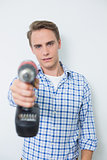 Portrait of a smiling handsome young handyman holding drill