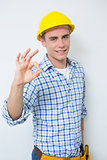 Portrait of a handyman in yellow hard hat gesturing okay sign
