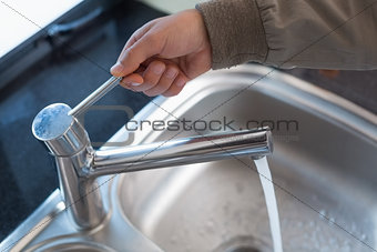Plumber's hand opening a water tap at bathroom