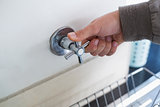 Plumber's hand opening a tap