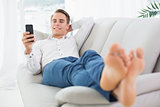 Relaxed man lying on sofa and text messaging