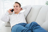 Relaxed man using cellphone while lying on sofa