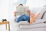 Relaxed man reading newspaper on sofa