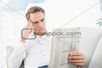 Serious relaxed man reading newspaper on sofa