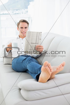 Relaxed man with coffee cup while reading newspaper on sofa