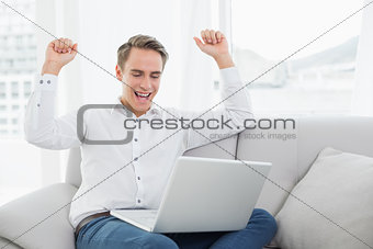 Casual young man using laptop while cheering on sofa