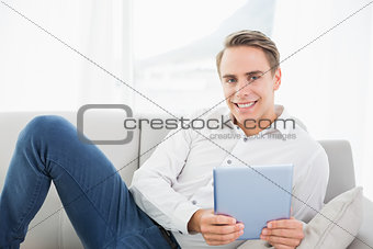Casual smiling young man using digital tablet on sofa