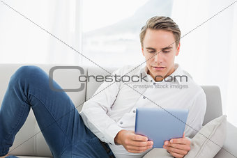 Casual young man using digital tablet on sofa