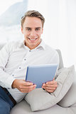 Portrait of a casual smiling man using digital tablet on sofa