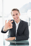Smiling businessman gesturing okay sign at office desk