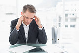 Businessman suffering from headache at office desk
