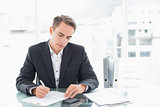 Businessman writing documents at office desk
