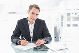 Smiling businessman writing documents at office desk