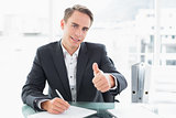 Businessman writing documents and gesturing thumbs up at office desk