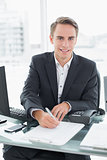 Businessman in front of computer writing document at office desk