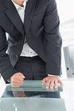 Mid section of businessman with clenched fist on office desk