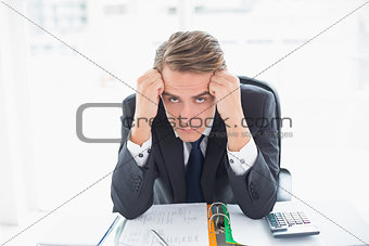 Portrait of worried businessman sitting at office desk