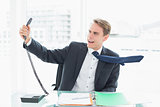 Businessman shouting as he holds out phone at office
