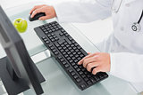 Mid section of doctor using computer