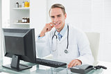 Confident doctor sitting with computer at medical office