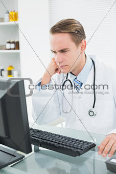 Serious doctor using computer at medical office