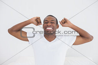 Afro man waking up in bed and stretching his arms
