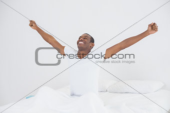 Smiling Afro man stretching his arms out in bed