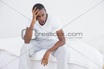 Afro man yawning in bed at home