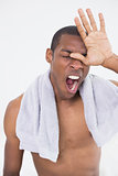 Close up of shirtless Afro man yawning with eyes closed