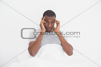 Afro man suffering from headache in bed